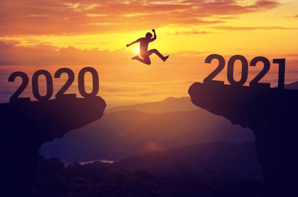 Silhouette man jump between 2020 and 2021 years with sunset background, Success new year concept. Silhouette man jump between 2020 and 2021 years with sunset background, Success new year concept. 2021 stock pictures, royalty-free photos & images