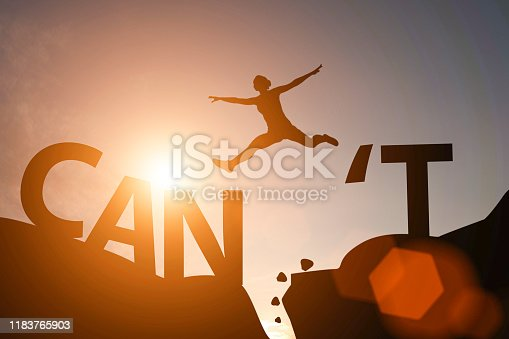 Silhouette man jump between can't wording and can wording on mountain. Mindset for career growth business.