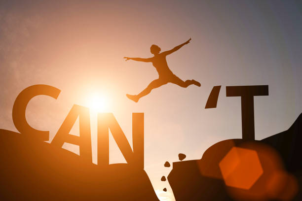 silhouette man jump between can't wording and can wording on mountain. mindset for career growth business. - superare le avversità foto e immagini stock