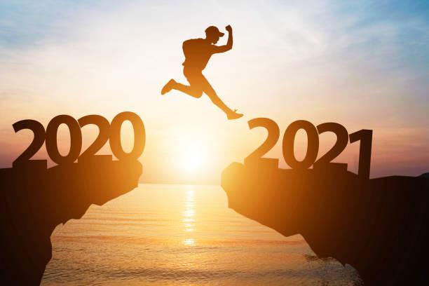 silhouette man hoppa från 2020 till 2021 på klippa med solljus för förändring och välkomna det nya året. - calendar workout bildbanksfoton och bilder
