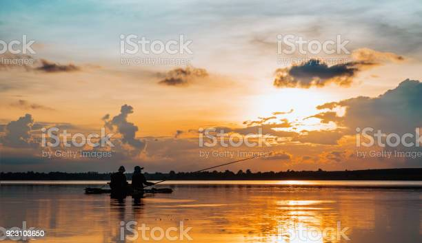 Photo of silhouette mature couple fishing over lake in sunset