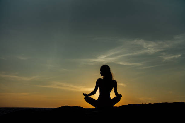Silhouette meditation girl lotus position on stone on the background of the stunning sea stock photo