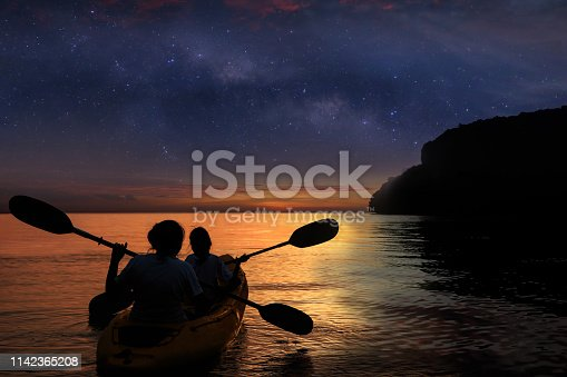 Silhouette mother and daughter kayaking in the ocean with million stars galaxy and sunrise sky early morning