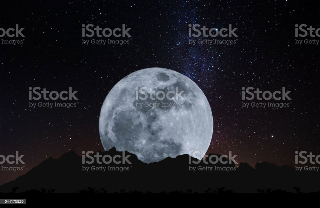 Silhouette mountain ridge with Full moon at night and the sky full of colorful stars stock photo