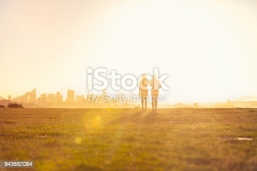 Silhouette of 2 women walking in the park. They are exercising an about to go running at sunset or sunrise with the city of Sydney in the background. One woman has her arm around the other. Could be a lesbian couple. Copy space