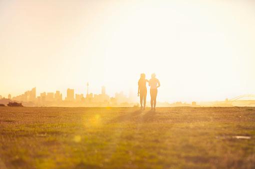 Silhouette of 2 women walking in the park.