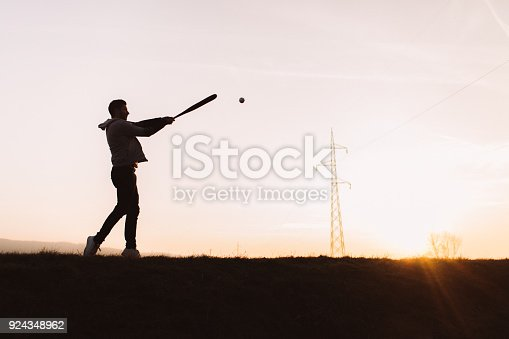 Silhouette portrait of a determined baseball player, practicing at sunset
