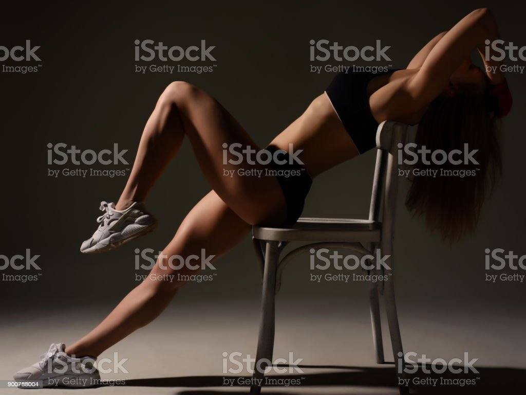 silhouette of a beautiful sports girl sitting on the edge of a chair straight legs stock photo