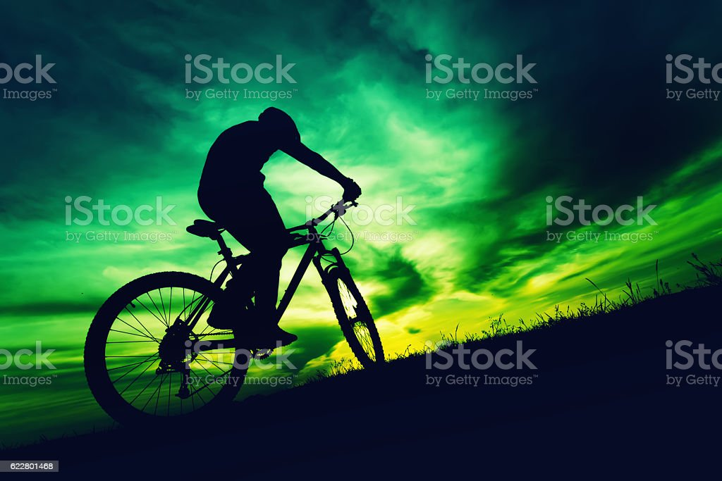 silhouette of a bicyclist against colorful sky at sundown stock photo