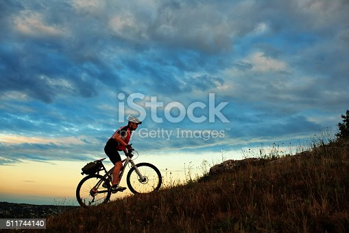 istock Silhouette of a biker and bicycle on sky background 511744140