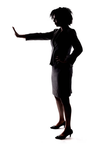 Silhouette of a Black Businesswoman Gesturnig Stop stock photo