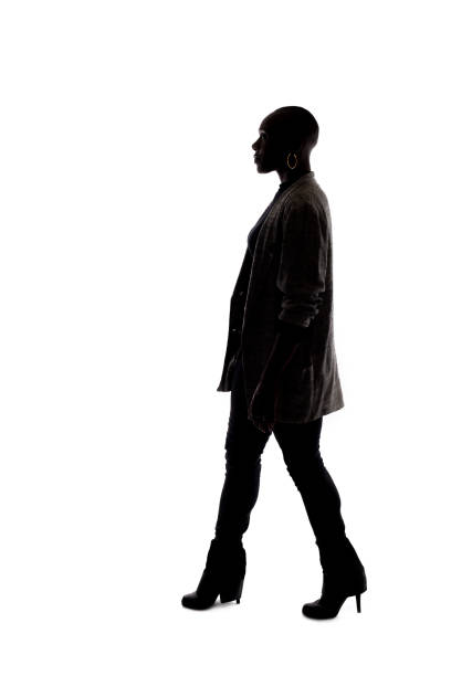 Silhouette of a Black Female Model on a White Background Walking stock photo