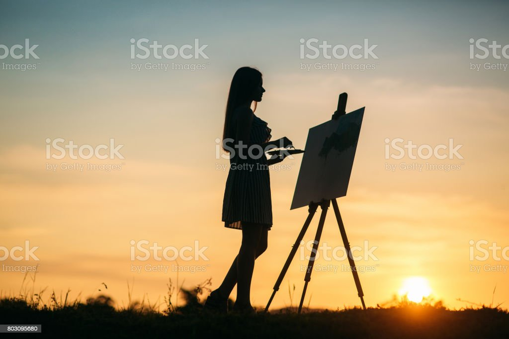 Silhouette of a blonde girl paints a painting on the canvas with the help of paints. A wooden easel keeps the picture. sunset stock photo