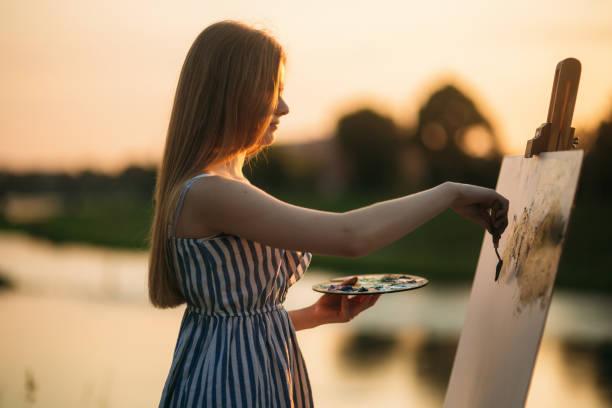 silhouette eines blonden mädchens malt ein bild auf der leinwand mit hilfe von farben. eine hölzerne staffelei hält das bild. sonnenuntergang - schönen abend bilder stock-fotos und bilder