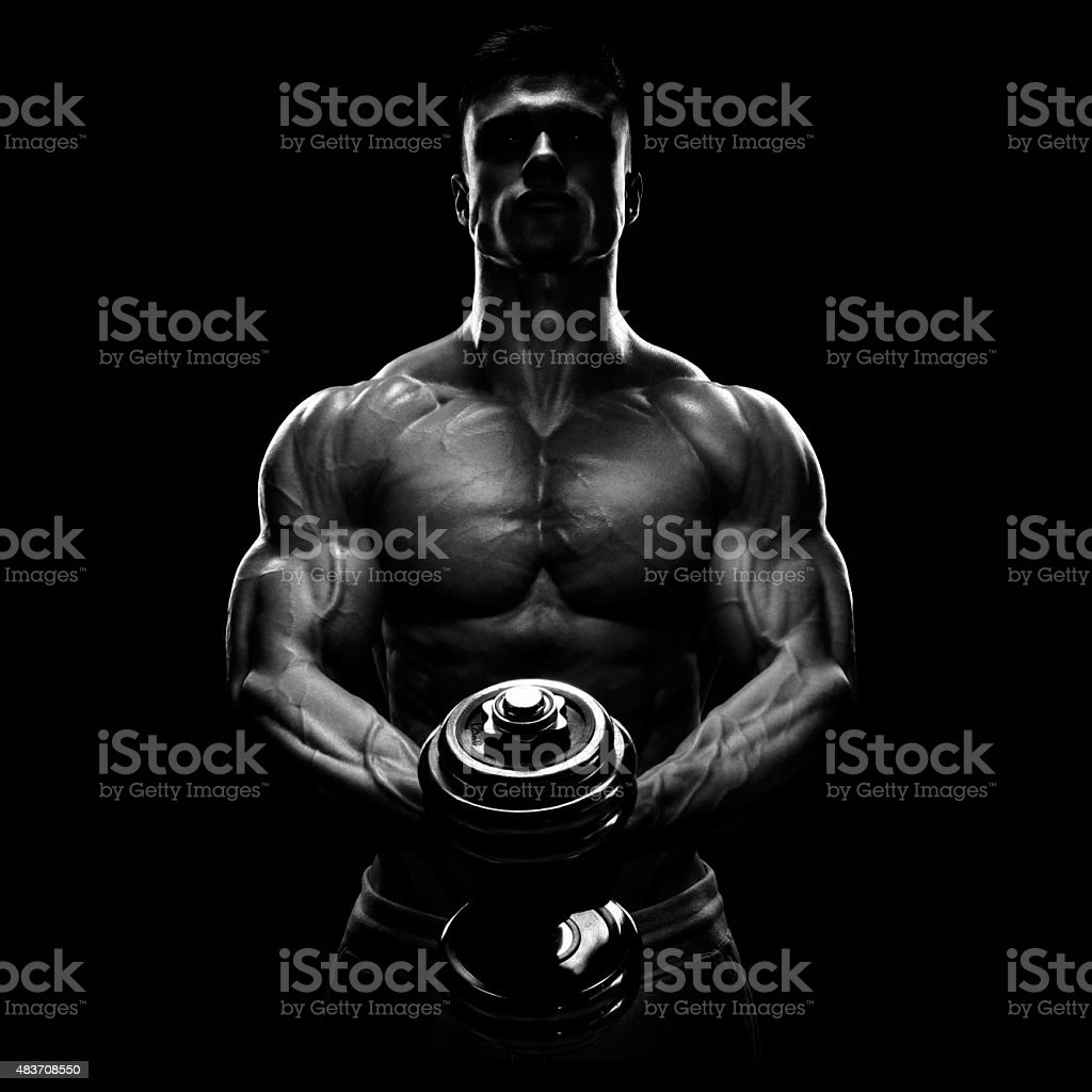 Silhouette of a bodybuilder pumping up muscles with dumbbell stock photo