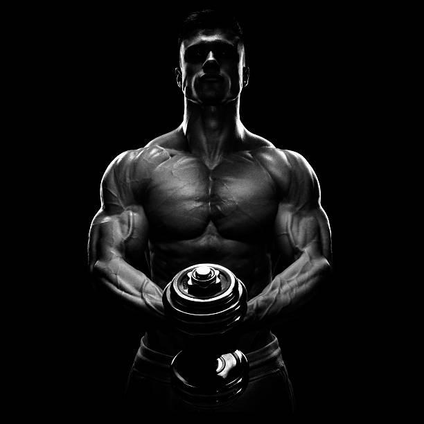 silueta de bodybuilder bombeo de los músculos con pesa - macho fotografías e imágenes de stock