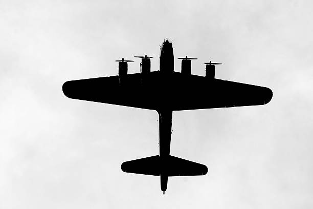 Silhouette of a bomber A backlit B-17G bomber passes overhead. bomber plane stock pictures, royalty-free photos & images