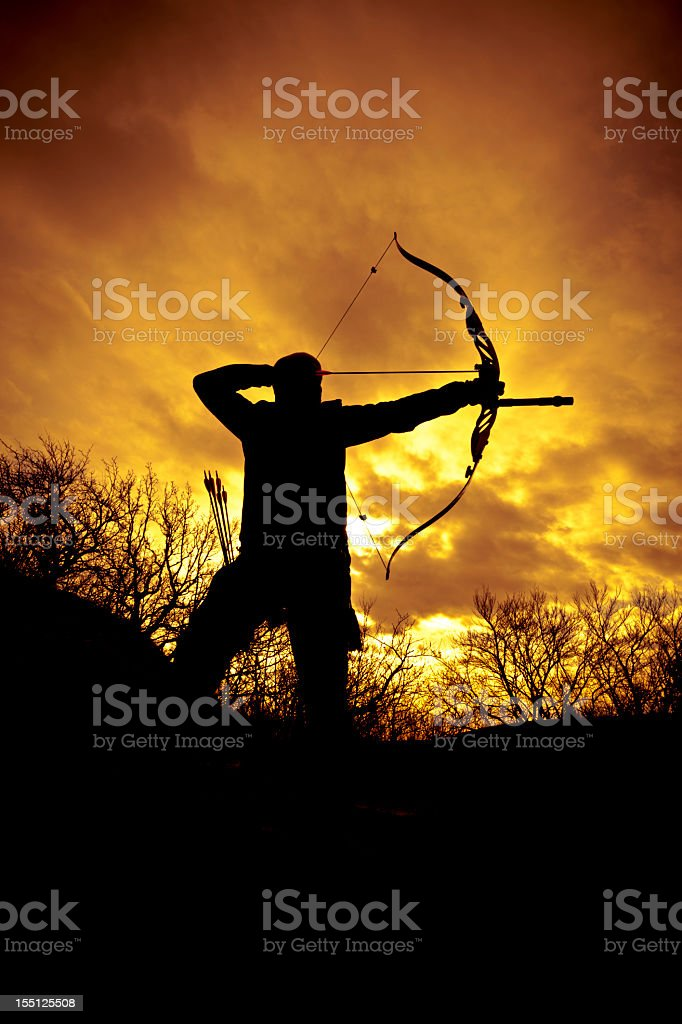 Silhouette of a bow hunter ready to shoot at sunset stock photo
