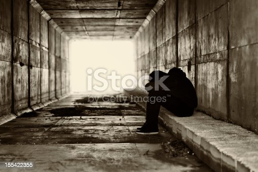 Boy sat in a corridor with the head covered