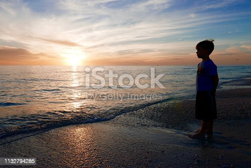 Silhouette of a young boy standing on a Florida gulf coast beach at the water's edge, looking at the sunset in the evening