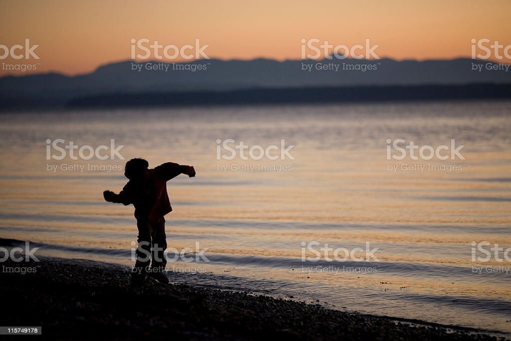 Silhouette of a boy skipping stones at dusk. stock photo