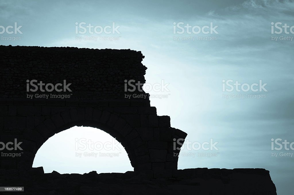 Silhouette of a broken bridge or aqueduct stock photo