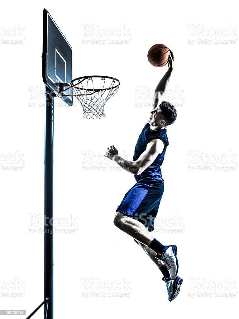 Silhouette of a caucasian male basketball player dunking stock photo