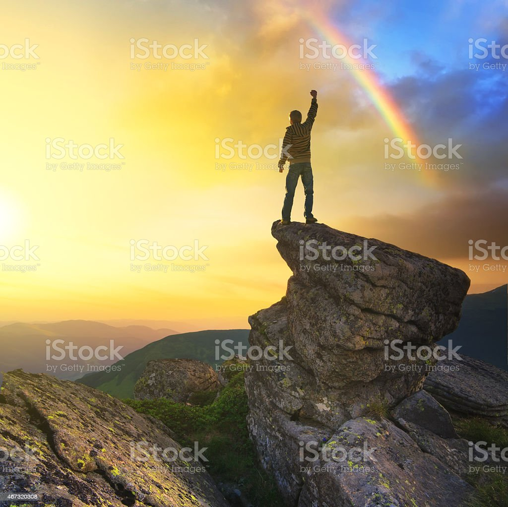 Silhouette of a champion standing on a cliff near rainbow stock photo