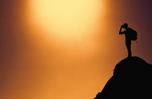 istock Silhouette of a climber on summit with copy space as symbol for success 990195240