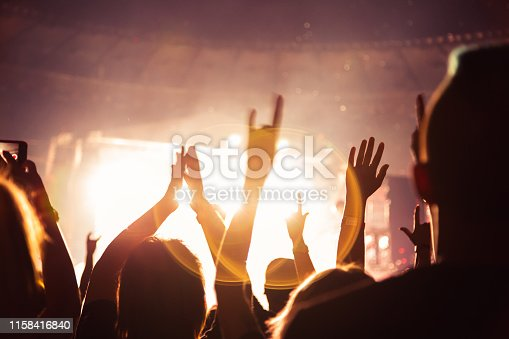istock Silhouette of a concert crowd. The audience applauds the musicians on stage. The bright spotlight and dancing people. 1158416840
