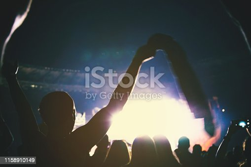 istock Silhouette of a concert crowd. The audience applauds the musicians on stage. The bright spotlight and dancing people. 1158910149