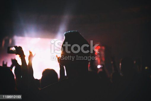 istock Silhouette of a concert crowd. The audience applauds the musicians on stage. The bright spotlight and dancing people. 1158910153