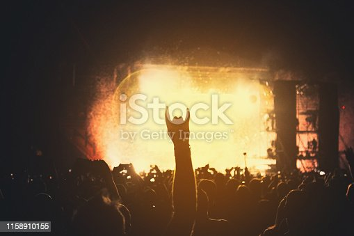istock Silhouette of a concert crowd. The audience applauds the musicians on stage. The bright spotlight and dancing people. 1158910155
