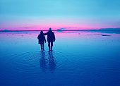 istock Silhouette of a couple enjoy walking on the flooding surface of Uyuni Salt Flats at sunset, Bolivia, South America 1263108271