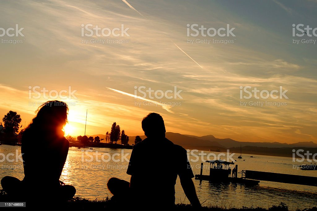 Silhouette of a couple enjoying the sunset. stock photo
