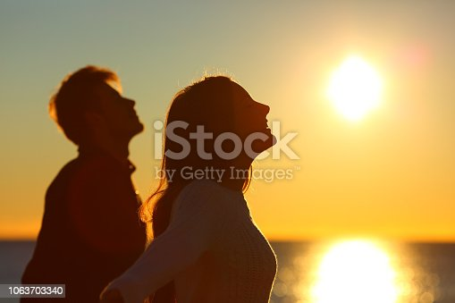 Silhouette of a couple of friends breathing deep fresh air at sunset on the beach