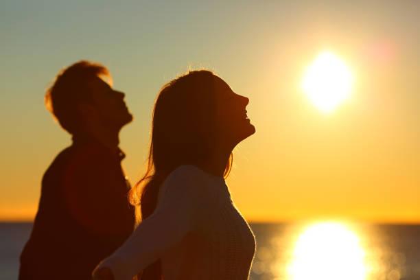 silueta de una pareja de amigos de respiración al atardecer - bienestar fotografías e imágenes de stock