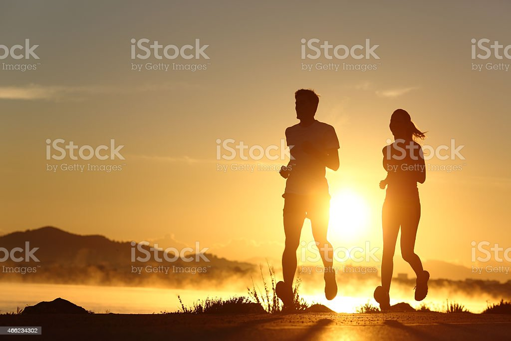 Silhouette of a couple running at sunset stock photo