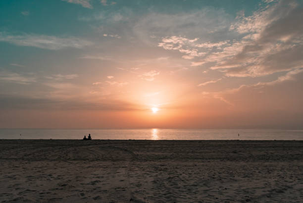 silhouette of a couple sitting on the sand watching the sun rise on a calm morning stock photo