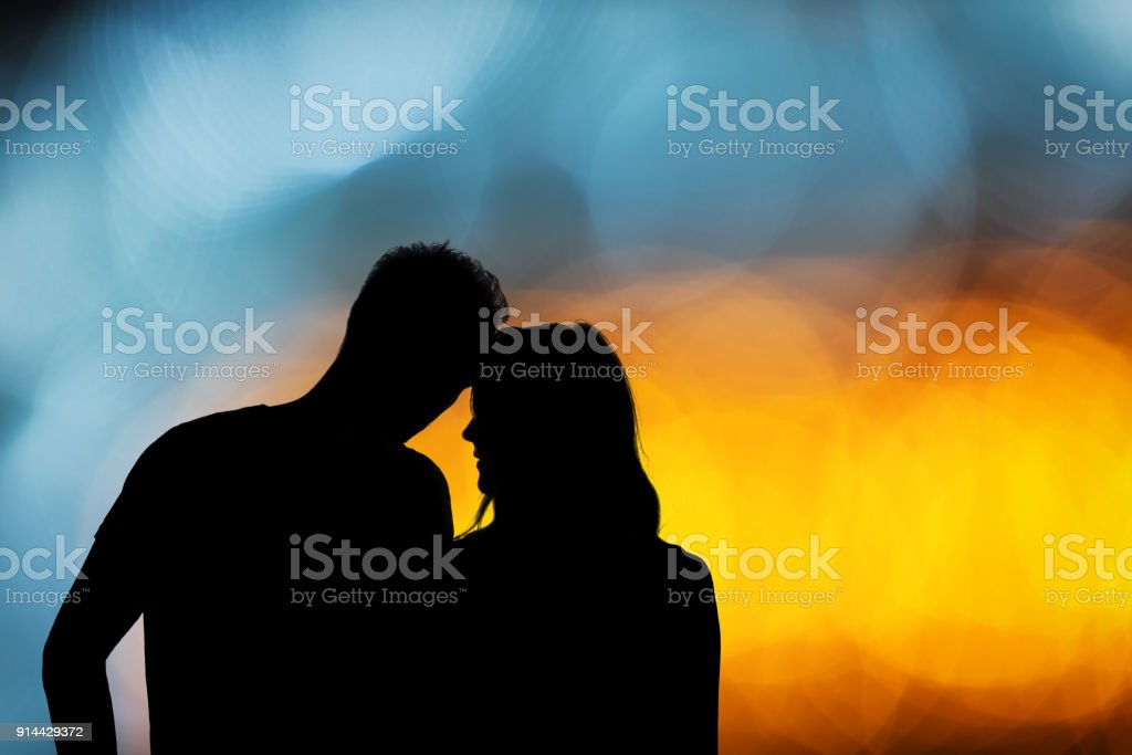 Silhouette of a couple with de-focused / bokeh lights. stock photo