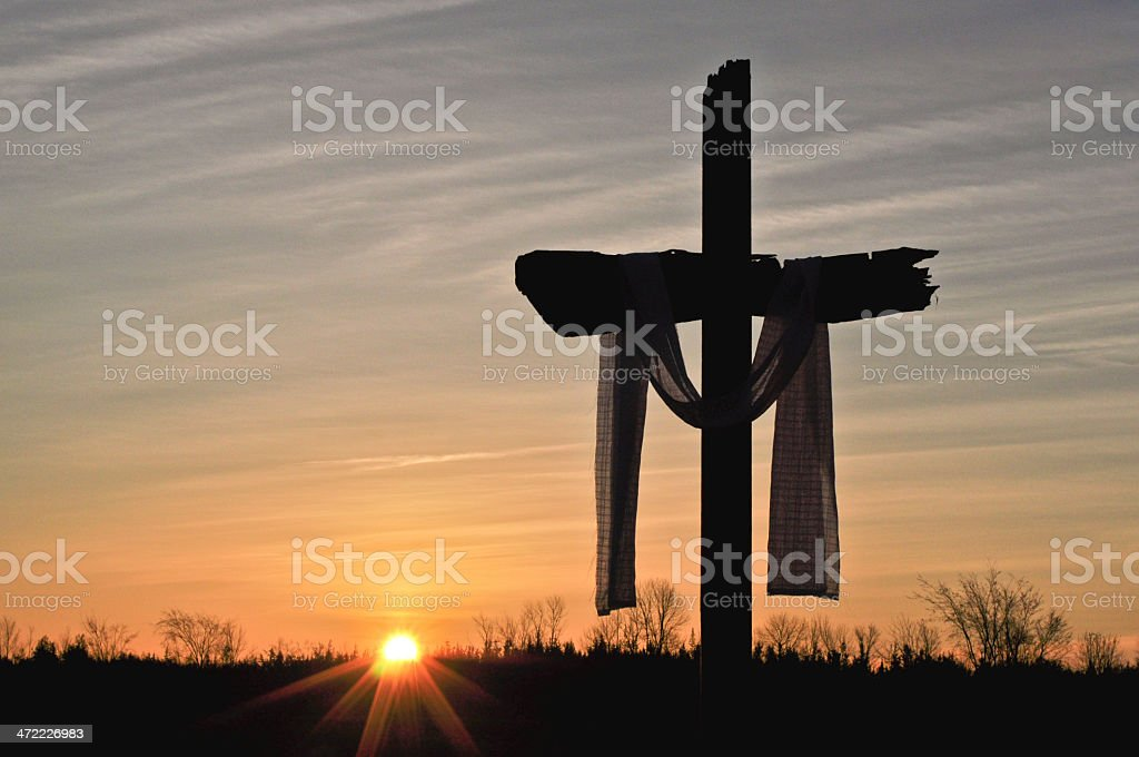 Silhouette of a crucifix at sunset stock photo