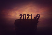 istock Silhouette of a determined man on the top of a cliff over sunset, announcing the new 2021 year coming, and throws out in the abyss the old 2020. Surreal seasonal scene, change concept and time control 1283848409