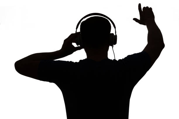 Silhouette of a DJ. He is raising his arms. stock photo