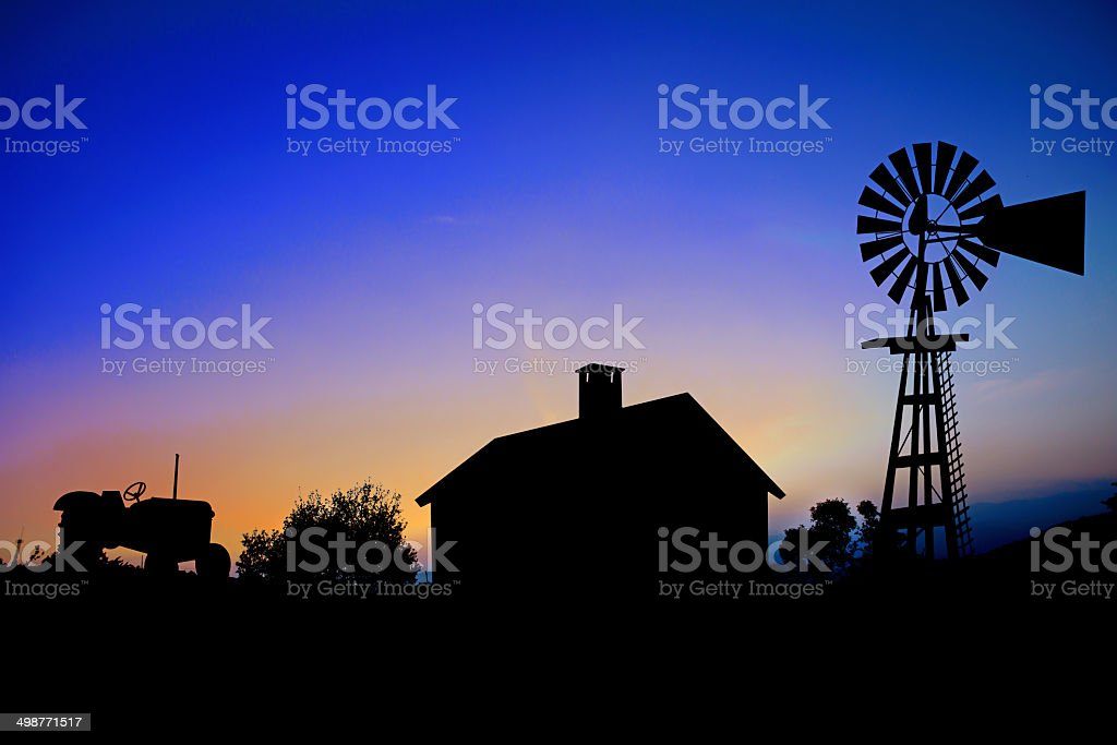 Silhouette of a farm tractor, house and windmill. stock photo