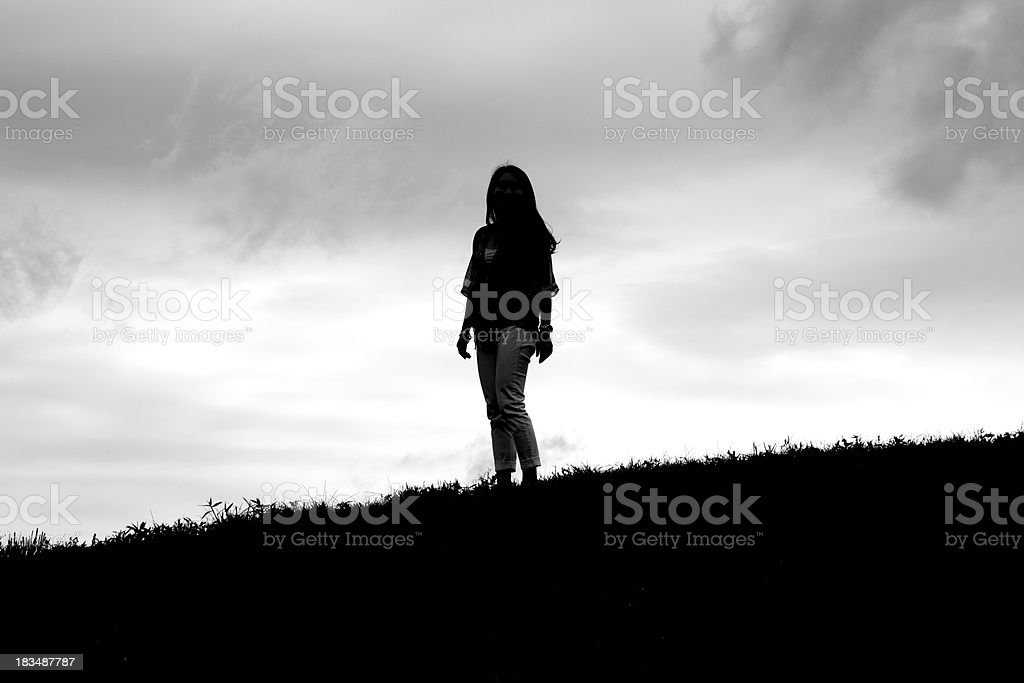 A silhouette of a female standing on top of a hill at dusk stock photo