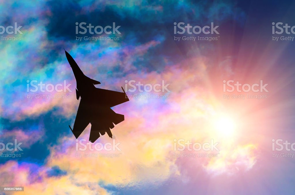 Silhouette of a fighter plane on a background of iridescent sky clouds and sun stock photo