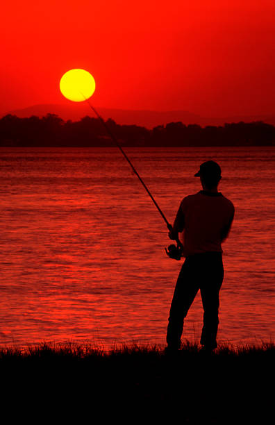 Silhouette of a fisherman at sunset stock photo
