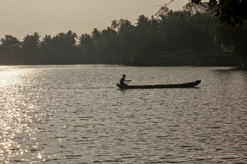Kollam, Kerala, India - January 2014: Silhouette of a fisherman on a wooden canoe in the waters of the Ashtamudi lake in Quilon.