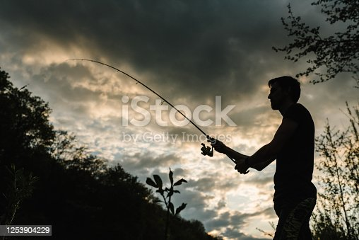 951984746 istock photo Silhouette of a fisherman. Young man fishing on a lake at sunset. Fishery, fishing day. Rod rings, fishing tackle. Fisherman with rod, spinning reel on the river bank. Fishing for pike, perch, carp. 1253904229