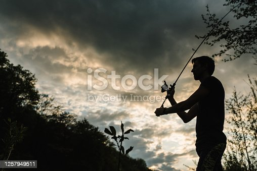 istock Silhouette of a fisherman. Young man fishing on a lake at sunset. Fishery, fishing day. Rod rings, fishing tackle. Fisherman with rod, spinning reel on the river bank. Fishing for pike, perch, carp. 1257949511